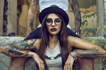 Gorgeous tattooed girl with provocative make up sitting between her boyfriend's legs in the ruined abandoned building, her arms on his knees. She is wearing black hat and glasses. Grunge style concept